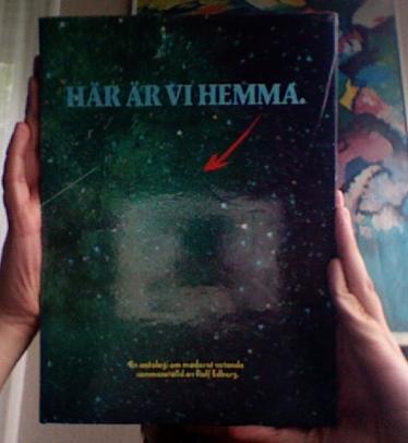 Två händer håller upp en bok med titeln